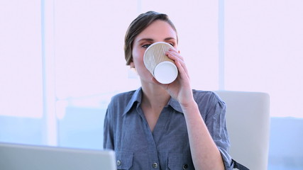 Happy businesswoman working on a laptop having a coffee