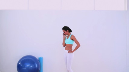 Fit woman talking on her phone and leaving