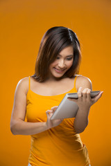 Happy Chinese Woman using a digital tablet.