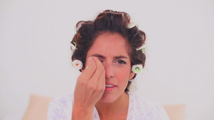 Concentrated woman in hair curlers plucking her eyebrow