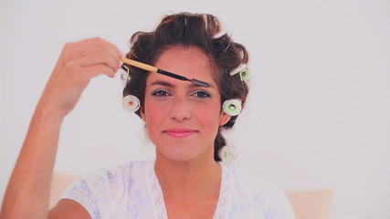 Smiling woman in hair curlers brushing her eyebrows