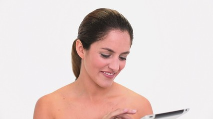 Amused brunette woman using a tablet pc