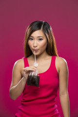 Asian woman with a drink in a bag on colorful background