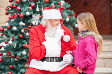 Girl Looking At Santa Claus Gesturing Finger On Lips