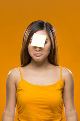 Forgetful Asian Woman with yellow sticky note on face