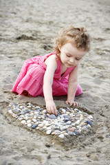 Little girl playing with shells on the beach