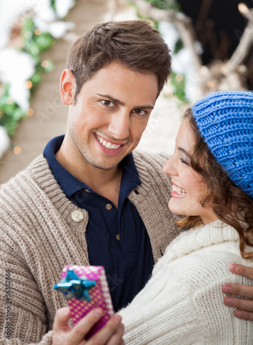 Happy Man Embracing Woman In Christmas Store