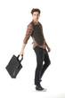 Full length mature casual man with bag walking in studio