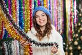 Young Woman Choosing Tinsels At Store