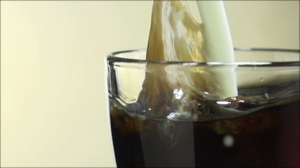 Milk being poured into glass coffee cup