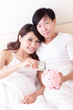 happy couple with pink piggy bank