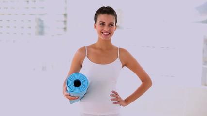 Motivated beautiful woman carrying a mat