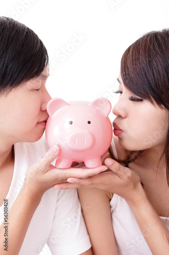 young happy couple kiss pink piggy bank