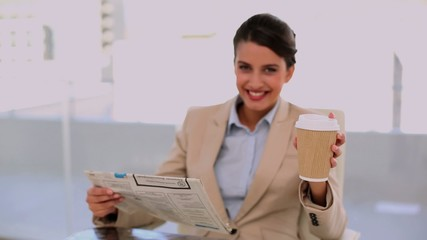 Relaxed businesswoman drinking coffee while reading newspaper