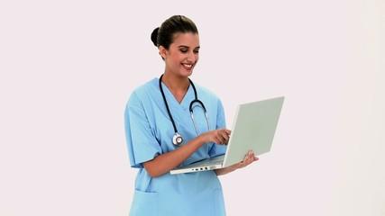 Amused beautiful nurse using a laptop