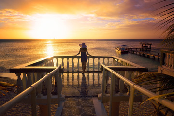A woman in a hat looking at the romantic Caribbean sunset