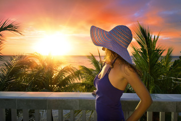 A woman on a balcony looking at the beautiful Caribbean sunset