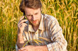 Farmer control wheat field while talking on mobile phone