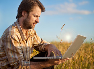 Modern farmer with laptop on his wheat field