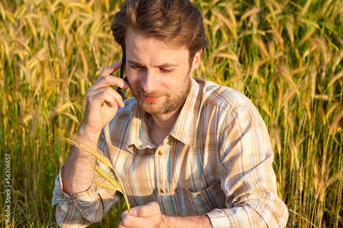 Happy farmer on wheat field talking on mobile phone