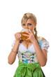 Junge Frau im Dirndl trinkt Bier