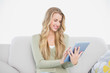 Happy pretty blonde using her tablet sitting on cosy sofa