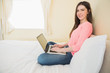 Happy girl looking at camera using a laptop sitting on a bed