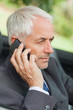 Serious businessman on the phone driving cabriolet