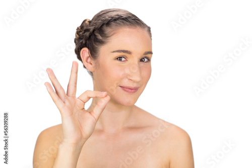 Cheerful woman making okay gesture