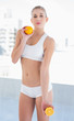 Serious young blonde model holding an orange and a half
