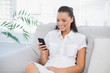 Cheerful woman sitting on sofa using phone