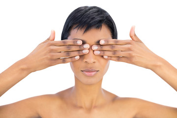 Serious black haired woman covering her eyes