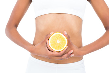 Close up of a fit model keeping half an orange