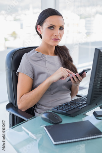 Serious businesswoman using calculator and looking at camera