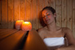 Happy brunette woman sitting in a sauna - 56311033