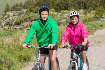 Happy couple on a bike ride wearing hooded jumpers