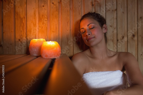 Happy brunette woman sitting in a sauna