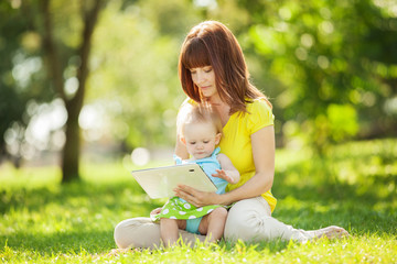 Happy family, mother and daughter with tablet resting in the par