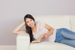 Happy asian girl lying on the sofa reading book smiling at camer