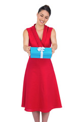 Smiling glamorous model in red dress offering present