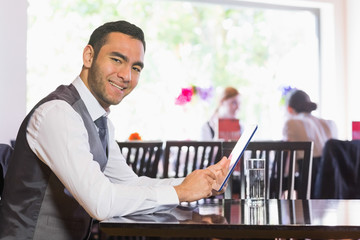 Happy businessman using tablet and smiling at camera