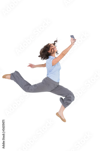 Happy classy businesswoman jumping while holding smartphone