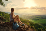 Girl sits on the edge of the cliff and looking at the sun