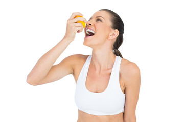 Sporty woman drinking juice from orange
