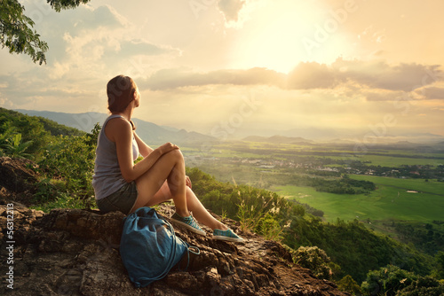 Fotobehang Alpinisme Girl sits on the edge of the cliff and looking at the sun