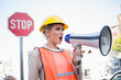 Businesswoman wearing builders clothes shouting in megaphone