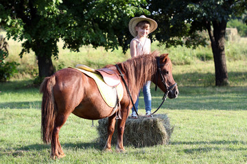 little girl with cowboy hat and pony horse pet