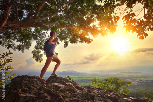Young woman admires the sunset with a backpack standing on cliff