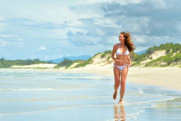 Happy woman running along the beach in Vietnam