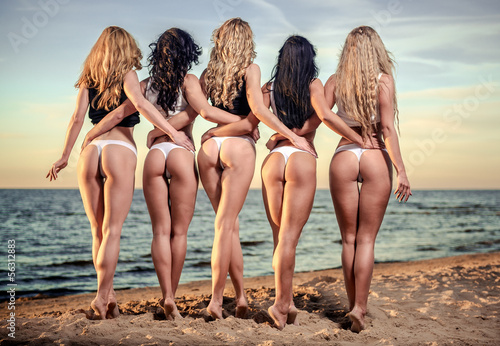 Sexy backs of five beautiful women in bikini on the beach